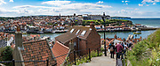 The Church Steps above Whitby: In Bram Stoker's famous 1897 novel, Dracula came ashore as a creature resembling a large dog who climbed the dramatic 199 Church Steps to the graveyard of Church of Saint Mary, adjacent to Whitby Abbey ruins atop East Cliff, above the Esk River. The Church of Saint Mary the Virgin is an Anglican parish church serving the towns of Whitby and Ruswarp in North Yorkshire county, England, United Kingdom, Europe. England Coast to Coast hike day 13 of 14. [This image, commissioned by Wilderness Travel, is not available to any other agency providing group travel in the UK, but may otherwise be licensable from Tom Dempsey – please inquire at PhotoSeek.com.] This image was stitched from multiple overlapping photos.
