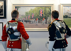 "© Licensed to London News Pictures. 20/04/2012. London, UK .Two soldiers look at The painting ""The Household Cavalry Mounted Regiment Escorting The Queen and Prince Philip Along The Mall after The Royal Wedding"" by Katie Scorgie. A Preview of the Household Cavalrys 'The Best of British' art exhibition. Soldiers walk around the artwork as they prepare to mount duties at Horse Guards Parade. The Queen's Life Guard are inspected before they depart the Barracks for the daily Guard change at 1100. The exhibition runs between 23 - 26 April. Hyde Park Barracks, Ceremonial Gate, South Carriage Drive, London, SW7 1SE. Photo credit : Stephen Simpson/LNP"