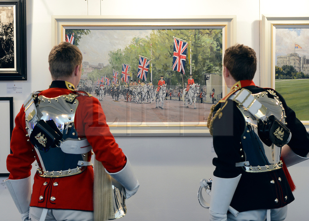 """© Licensed to London News Pictures. 20/04/2012. London, UK .Two soldiers look at The painting """"The Household Cavalry Mounted Regiment Escorting The Queen and Prince Philip Along The Mall after The Royal Wedding"""" by Katie Scorgie. A Preview of the Household Cavalrys 'The Best of British' art exhibition. Soldiers walk around the artwork as they prepare to mount duties at Horse Guards Parade. The Queen's Life Guard are inspected before they depart the Barracks for the daily Guard change at 1100. The exhibition runs between 23 - 26 April. Hyde Park Barracks, Ceremonial Gate, South Carriage Drive, London, SW7 1SE. Photo credit : Stephen Simpson/LNP"""