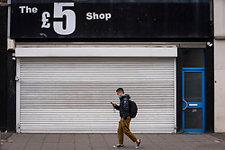 © Licensed to London News Pictures. 17/10/2020. LONDON, UK. A man wearing a facemask passes a closed £5 shop in Ealing, west London.  The Office for National Statistics (ONS) has reported that the confirmed coronavirus cases in the capital exceed 67,000, with Ealing having the highest Covid-19 rate amongst London Boroughs at 144 cases per 100.  Following the UK Government's announcement, the capital has today moved from Tier 1 to Tier 2, meaning a ban on indoor social mixing between households in the capital.  Photo credit: Stephen Chung/LNP