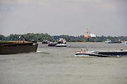 Nederland, Nijmegen, 11-6-2020 Het water in de waal zakt langzaam vanwege de aanhoudende droogte in haar stroomgebied. Binnenvaartschepen varen langs de Ooijpolder . Langzaam daalt het peil van het water in de rivier . Het is druk op de rivier. Een zesbaks duwcombinatie geladen met kolen, steenkool, vaart richting Duitsland . In de herfst van 2018 stond de stand bij Lobith op 6,55 meter boven nap, een laagwater record dat veel overlast voor de binnenvaart opleverde .. . Foto: Flip Franssen