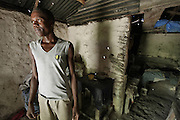 A man stands in his home in the mountainside above Carrefour, Haiti.  His bedroom can be seen in the background.  Most of the mountain people live in homes that are made with sticks covered with plaster.  With over 2/3 of the population unemployed, the future looks bleak.