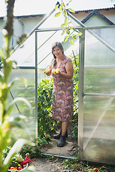 Senior woman with harvested pepper in a greenhouse, Altoetting, Bavaria, Germany