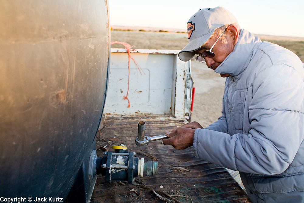 22 OCTOBER 2007 -- COYOTE CANYON, NM: MARK TSOSIE, 78 years old, a member of the Navajo Nation, fills a water tank on the back of his GMC pickup truck to haul water from a well to his home and his livestock. Tsosie has been hauling water all his life. He started working for the railroad when he was 14 years old. His job was to haul water to the workers. Now retired and he's still hauling water except now he hauls it to his home. More than 30 percent of the homes on the Navajo Nation, about the size of West Virginia and the largest Indian reservation in the US, don't have indoor plumbing or a regular supply of domestic water. Many of these homes have to either buy water from commercial vendors or haul water from public wells. A Federal study showed that the total cost of hauling water was about $113 per 1,000 gallons. A Phoenix household, in comparison, pays just $5 a month for up to 7,400 gallons of water. The lack of water on the reservation means the Navajo are among the most miserly users of water in the United States. Families that have to buy or haul water use only about 15 gallons of water per day per person. In Phoenix, by comparison, the average water use is about 170 gallons per day.  Photo by Jack Kurtz