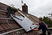 Solar PV Photo Voltaic panels being installed on roof of a home. PV cells convert sunlight into electrical energy.