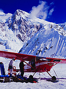 K2 Aviation's Cessna 185 on wheel skis at the Southeast Fork of the Kahiltna Glacier Base Camp, Mount Hunter beyond, Denali National Park, Alaska.