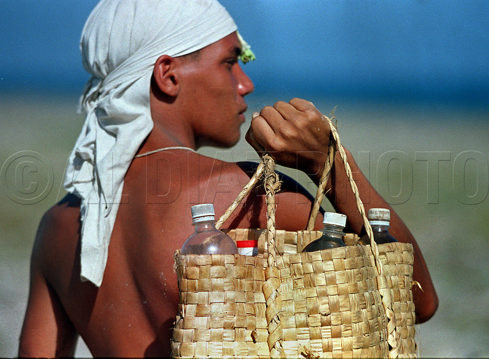 In 1994 Cuban balseros turned the tiny fishing village of Cojimar into a major point of embarkation for thousands seeking a better life. Here, Alex Castillo del Campo, 18, carries bottles of water in preparation of his long voyage on a makeshift raft departing Cojimar Cuba. He wrapped a cloth around his head to protect himself from sunburn. Many of the rafters died of thirst, sun exposure or shark attack. Some developed skin ulcers, similar to bed sores, as a result of clinging to the sides of inner tubes. Others suffered from hypothermia, because the water, while warm at that time of year, was still below body temperature. Many, suffering hallucinations, jumped off their rafts.