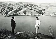 two men standing on top of a ridge looking out over a lake and mountainous desert landscape Morocco 1930s