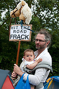 Balcombe, West Sussex. Site of Cuadrilla drilling. Demonstration against fracking 18.08.2013. A protester holds his baby and a sign saying 'Hit the road Frack'.