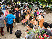 "21 JULY 2013 - BANGKOK, THAILAND:   The families of men entering the monastery for Vassa have their hair cut by members of their families at Wat Benchamabophit on the first day of Vassa, the three-month annual retreat observed by Theravada monks and nuns. Men frequently enter the monastery and become Buddhist monks for Vassa. On the first day of Vassa (or Buddhist Lent) many Buddhists visit their temples to ""make merit."" During Vassa, monks and nuns remain inside monasteries and temple grounds, devoting their time to intensive meditation and study. Laypeople support the monastic sangha by bringing food, candles and other offerings to temples. Laypeople also often observe Vassa by giving up something, such as smoking or eating meat. For this reason, westerners sometimes call Vassa the ""Buddhist Lent.""      PHOTO BY JACK KURTZ"