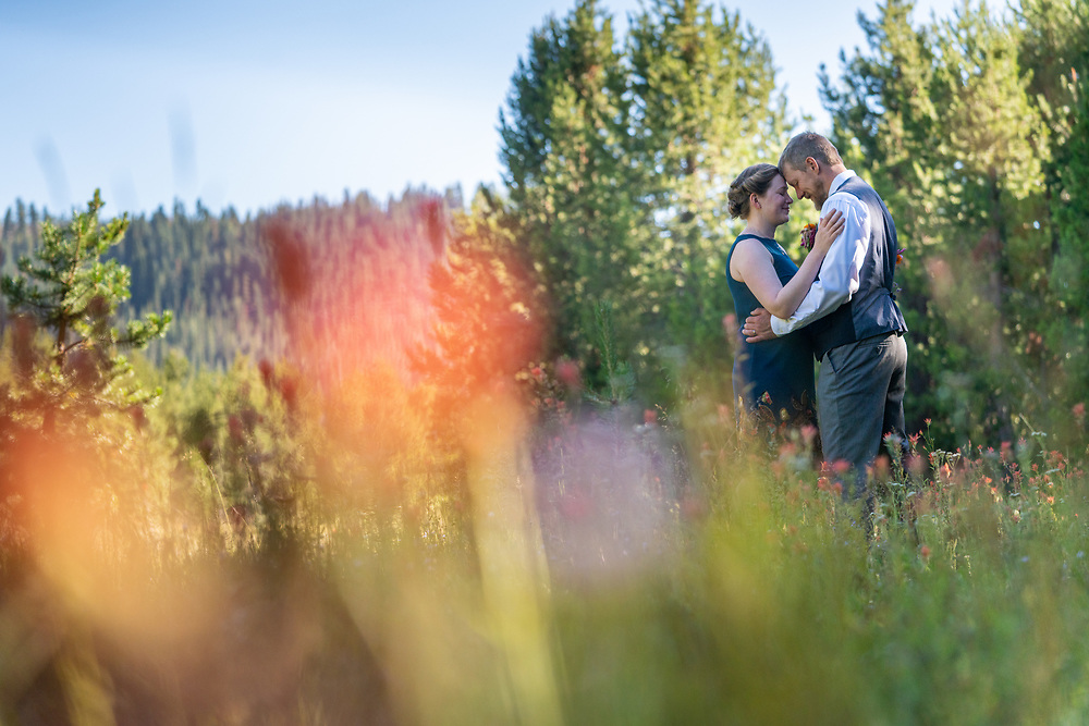 Post ceremony meadow embrace with an out of focus wildflower foreground.