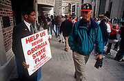 An African-American Georgia flag protestor holds his placard to a white passer-by before the Atlanta Braves World Series baseball victory parade, on 5th November 1995, in Atlanta, Georgia USA.. James Coleman brought this action to enjoin the flying of the Georgia state flag over Georgias state office buildings. Coleman, an African-American, alleges that the flying of the Georgia flag, which incorporates the Confederate battle flag emblem, violates his constitutional rights to equal protection and freedom of expression.