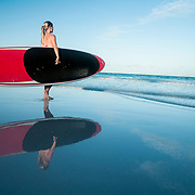 A woman standing on a beach ready to go paddle boarding. Image made on Harbour Island, Bahamas.