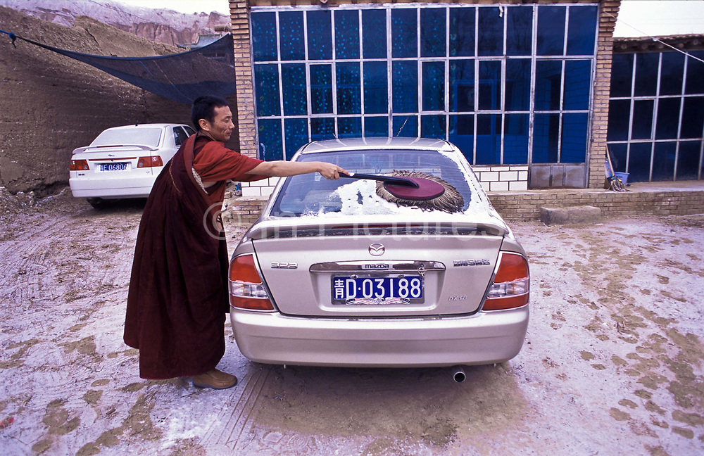 Tibetan buddhist monk Dongyu, removes the night's covering of snow off his car, which waas given to him by his parents in front of his small but well furnished  and equiped living space comprising of a living room / bedroom and a  wood fired kitchen in side the complex of the 300 years old Atsog Monastery, Xinghai County, Qinghai Province, China.
