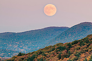 The nearly full moon rises over the Hudson Highlands and Schunnemunk Mountain, in the foreground, as seen from Salisbury Mills, New York.