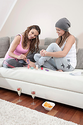 Young woman varnishing toenails of her female friend at home