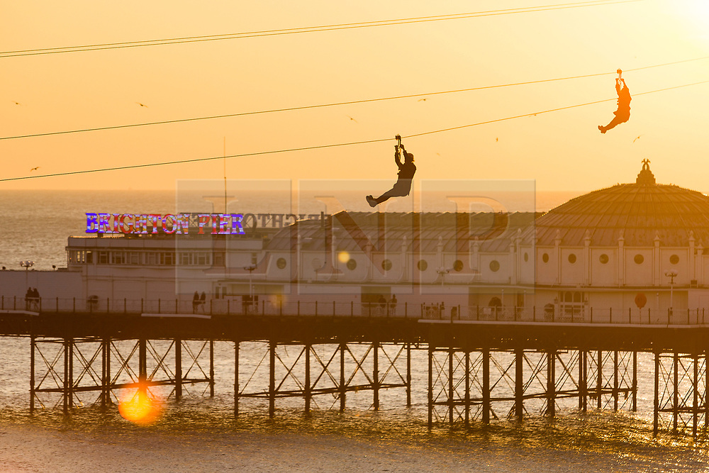 © Licensed to London News Pictures. 24/02/2018. Brighton, UK. Members of the public ride the Brighton Zip Wire on the beach as a golden sun sets behind the Palace Pier in Brighton and Hove, today Saturday 24th February 2018. Photo credit: Hugo Michiels/LNP