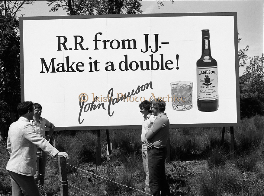 President Reagan Visits Ireland..Advertising Campaign.1984.04.06.1984.06.04.1984.4th June 1984..Availing of the opportunity of the President Reagan visit, the Whiskey manufacturers advertised their wares.Photo shows a large billboard encouraging RR (Ronald Reagan) to have a double. Passers by discuss the billboard, Jameson's, Irish, Whiskey, jameson,