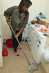 Teenage girl mopping kitchen floor. (This photo has extra clearance covering Homelessness, Mental Health Issues, Bullying, Education and Exclusion, as well as the usual clearance for Fostering & Adoption and general Social Services contexts,)