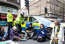 London, UK. 16th April 2019. A police officer asks a man who had been praying at a religious service in Edgware Road for access to his vehicle during the second day of International Rebellion UK activities by climate campaigners from Extinction Rebellion to call on the Government to take urgent action to address climate change.