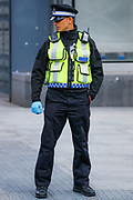 A community police officer is seen making a gesture while waiting in the traffic lights wearing protective surgical gloves and bearing a hand-sanitizer on his chest near Tottenham Court Road underground station in central London on Monday, May 11, 2020. <br />