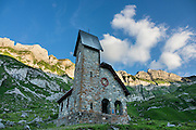 """Sunset at Meglisalp brightens peaks behind a 1904 mountain chapel (Kapelle Maria zum Schnee, """"Holy Mother Mary of the Snow""""). Berggasthaus Meglisalp can only be reached on foot in the heart of the Alpstein mountain chain in the Appenzell Alps, Switzerland, Europe. This authentic mountain hostelry, owned by the same family for five generations, dates from 1897. Meglisalp is a working family dairy farm."""