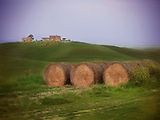 Bails of hay are gathered at the bottom of a hill on an Italy farm