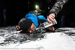 The happiest Frenchman, Fred Billon on the frozen lake to make a Baikal Kiss (drill a hole in the ice and fill it with vodka to drink) during the wrap party after the Baikal Mile Ice Speed Festival. Maksimiha, Siberia, Russia. Saturday, February 29, 2020. Photography ©2020 Michael Lichter.