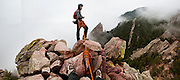 Ethan Welty belays Obadiah Reid on the summit of the First Flatiron above Boulder, Colorado, rising above the mist.