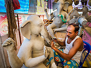 06 SEPTEMBER 2018 - BANGKOK, THAILAND: The lead artisan of a crew of Indian craftsmen works on a statue of Ganesh at Wat Witsanu Hindu Temple in Bangkok. Indian craftsmen are making statues of the Hindu deity Ganesha for the Ganesh Chaturthi, or Ganesh Festival, held at Hindu temples in September. All of the craftsmen, and the clay they use to fashion the statues, come to Thailand from India every year to make the statues. Although Thais are predominantly Buddhist, the Lord Ganesh, the Hindu overcomer of obstacles, is worshipped by many Thais and Ganesh Chaturthi is celebrated in many Thai communities.     PHOTO BY JACK KURTZ