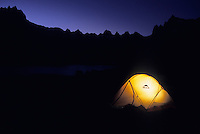 A tent glows at dusk in Titcomb Basin, Wind River Mountains, Wyoming.