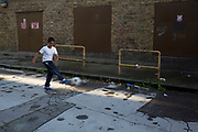 Young Asian boy playing football on his own in an empty street in Whitechapel, East London, UK. This is a mainly Bengali / Bangladeshi area.