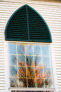 Church window panes reflect autumn colors, evening light, October, Cheshire County, New Hampshire, USA