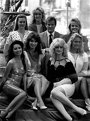 """File photo dated 01/06/83 of Roger Moore in London with seven of the girls who will appear in the James Bond film """"Octopussy"""". Sir Roger has died in Switzerland after a short battle with cancer, his family has announced."""