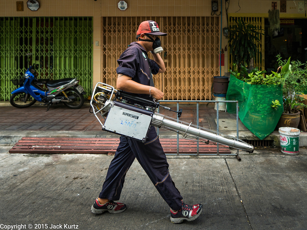 02 DECEMBER 2015 - BANGKOK, THAILAND:  A health department mosquito control worker walks down a street in a neighborhood in Bangkok. The Public Health Ministry in Thailand said that more than 111,000 cases of dengue fever have been reported in 2015, an increase of more than 200% over the number of cases of dengue fever reported 2014. Dengue fever is a virus spread by mosquito and is endemic in southeast Asia. Thai health officials are aggressively spraying areas where mosquitoes are known to live and leading public information and education sessions on preventing dengue fever. There is no vaccine for dengue fever, so preventing dengue means avoiding mosquitoes.       PHOTO BY JACK KURTZ