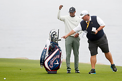 June 12, 2019 - Pebble Beach, CA, U.S. - PEBBLE BEACH, CA - JUNE 12: PGA golfer Tiger Woods looks at the clubs of Kevin Kisner  while talking to Kisner's caddie Duane Bock on the 18th hole during a practice round for the 2019 US Open on June 12, 2019, at Pebble Beach Golf Links in Pebble Beach, CA. (Photo by Brian Spurlock/Icon Sportswire) (Credit Image: © Brian Spurlock/Icon SMI via ZUMA Press)