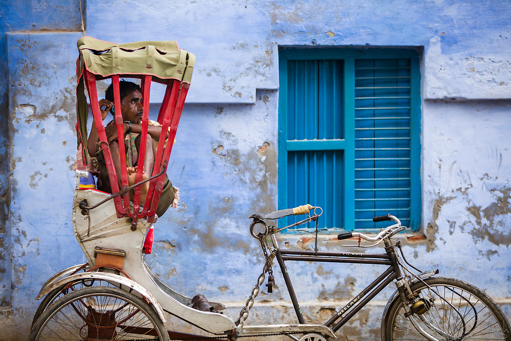 A cycle rickshaw driver taking a break from work, sitting in the seat of his rickshaw, High Street, Varanasi, India