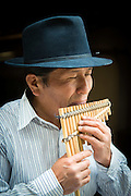 Jose Luis Fichamba plays a rondador or panpipe made from bamboo in his workshop, Peguche , Otavalo, Ecuador, South America