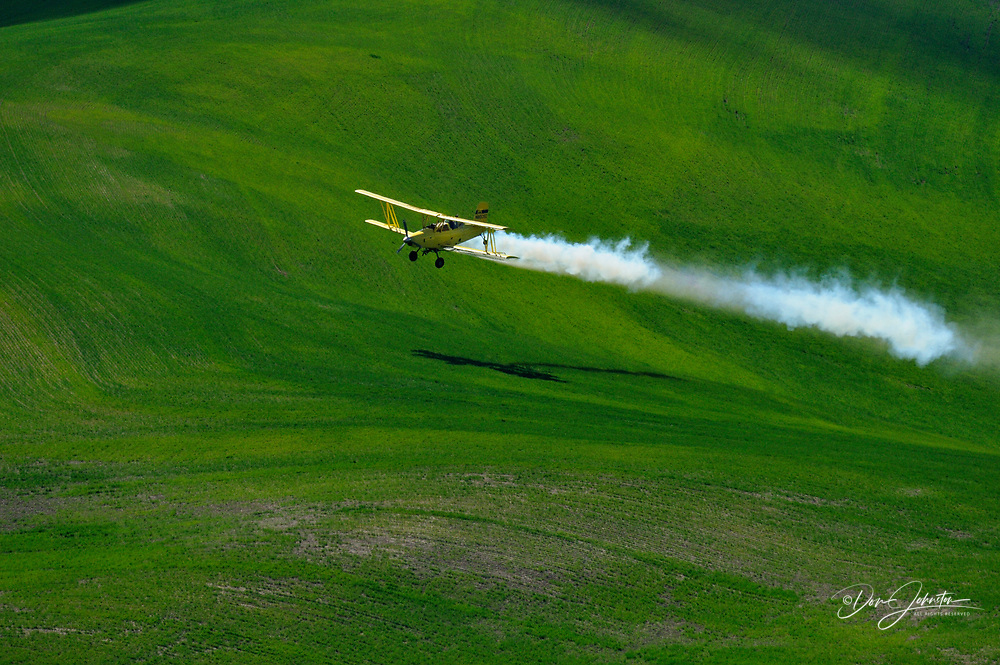 Crop duster aircraft spraying Palouse farmland, Steptoe Butte State Park, Washington, USA