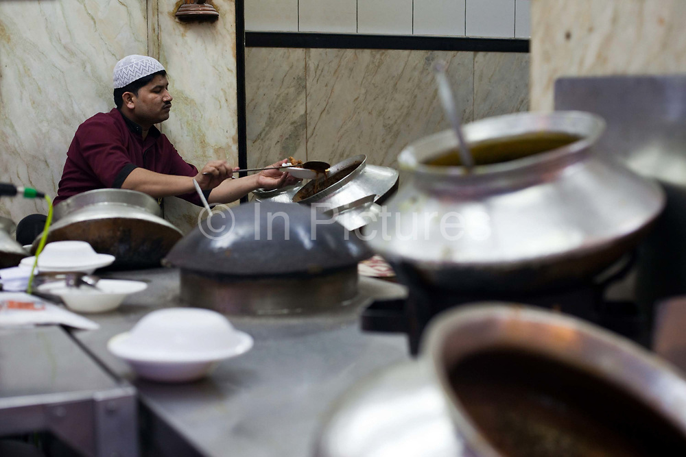 A man serves curries from huge pots in the courtyard at Karims Restaurant, Old Delhi