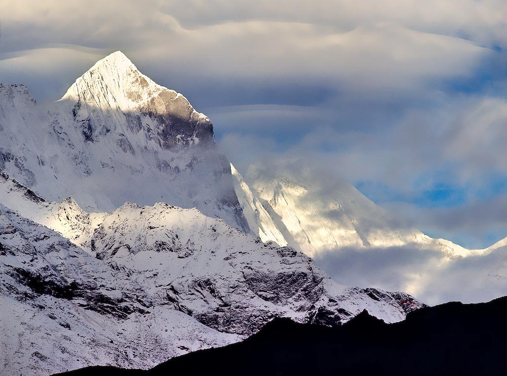 Clouds collect above Kwangde Peak in the Khumbu Himalaya in Sagarmatha National Park, Nepal.