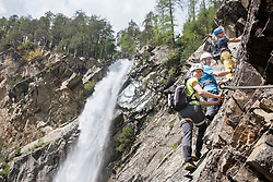Men climbing on rock via ferrata towards Lehner Waterfall, Otztal, Tyrol, Austria