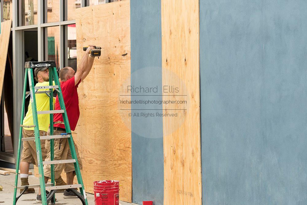 Workers attach hurricane shutters to a shop window on historic King Street shopping district in preparation for approaching Hurricane Florence September 11, 2018 in Charleston, South Carolina. Florence, a category 4 storm, is expected to hit the coast between South and North Carolina and could be the strongest storm on record for the East Coast of the United States.