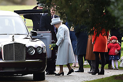 Queen Elizabeth II carries daffodils given by a girl (right) after attending the morning church service at St Mary Magdalene Church in Sandringham, Norfolk.