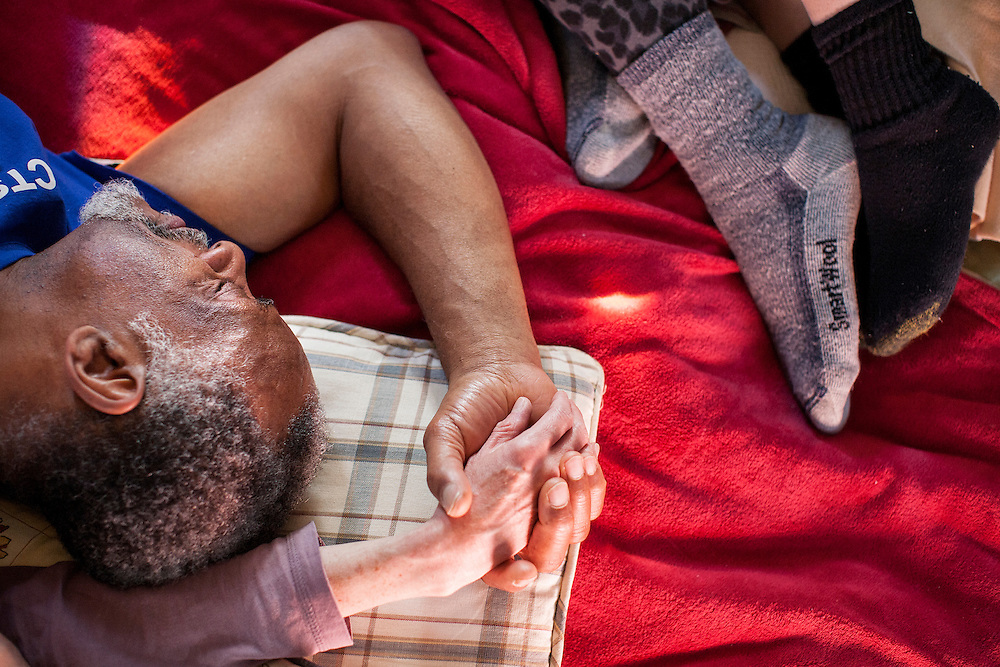 David Byrd holds another participant's hand as they lay with others, cuddling on a blanket-covered floor during a Cuddle Party at a home in Minneapolis January 9, 2015. The gatherings have strict rules to keep the event safe and respectful.