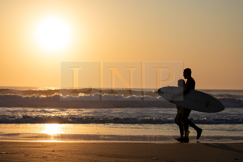 © Licensed to London News Pictures. 26/03/2020. Wadebridge, UK. A surfer and a walker on Constantine Bay beach, Cornwall during sunset this evening. British Prime Minister Boris Johnson yesterday ordered a lockdown to slow the spread of Coronavirus (COVID-19) across the country. Photo credit : Tom Nicholson/LNP