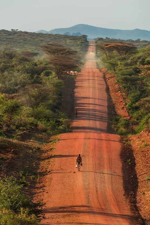 Hamer tribe man walking down long dirt road in the Omo Valley, Ethiopia.