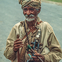 A village musician with his homemade violin waits to entertain bus travelers in Nepal.