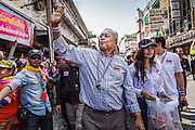 05 JANUARY 2014 - BANGKOK, THAILAND:  SUTHEP THAUGSUBAND, leader of the anti-government movement, greets the crowd during a march through Bangkok Sunday. Suthep is a former Deputy Prime Minister and member of the opposition Democrat Party who resigned to organize the protests against the Pheu Thai government.  He led the protestors on a march through the Chinatown district of Bangkok. Tens of thousands of people waving Thai flags and blowing whistles gridlocked what was already one of the most congested parts of the city. The march was intended to be a warm up to their plan by protestors to completely shut down Bangkok starting Jan. 13.    PHOTO BY JACK KURTZ