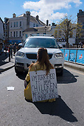 """Abbey, a 24 year-old part-time waitress and self-employed dressmaker joined over 200 hundred Extinction Rebellion activists who sat alone in roads blocking oncoming traffic in a courageous attempt to highlight the current climate crisis at 11am on Saturday 1st May 2021, in Newquay, Cornwall, United Kingdom. The 'sitters' from across the country wore signs with a message about their fears for the future if the climate and ecological crises continues to go unaddressed. The individual disruptive actions took place in towns and cities across the UK.<br /> <br /> The action was part of an approach developed during the Covid-19 pandemic by members of Extinction Rebellion, in which people can engage in civil disobedience alone, yet united.<br /> <br /> Abbey, from Newquay, who blocked traffic on a local road, said: """"At school I excelled in science and science is taught as the reality, as fact, as truth. I wanted to be a scientist, I wanted to be Prime Minister, but my most cherished aspiration was to be a mother. This dream was taken from me when I read headlines in 2018 stating that we were 12 years away from hitting devastating climate tipping points. These headlines were referencing a report released by the Intergovernmental Panel on Climate Change: scientists. The kind of report I was taught to hold with high regard as truth at school. I realised that climate change was not someone else's problem. Ecosystem collapse, flooding, food shortages, mass migration are crises that both this and the next generation will face if this government fails to act now. Two years have passed since that report was released and May 1st marks two years since Parliament declared an environment and climate emergency, yet this government is ploughing further into this catastrophe. My dream of being a mother has been taken from me by politicians set on business as usual. I am blocking traffic as I grieve children I will not conceive."""""""
